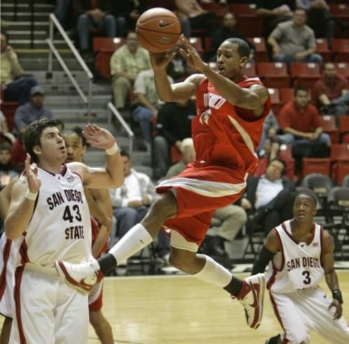 New Mexico's J.R. Giddens jumps through the San Diego State defense as he splits between Richie Williams, right, and Ryan Amoroso.