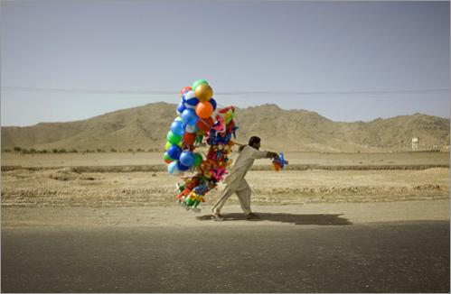 An Afghan man carries a bundle of balloons as he walks along a street on the outskirts of Kabul, Afghanistan, Friday, June 27, 2008.