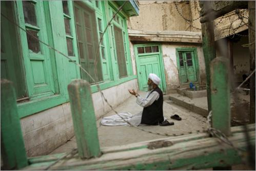An elderly Afghan man prays outside a mosque in Kabul, Afghanistan, Thursday, June 26, 2008.