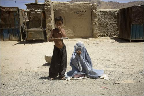 An Afghan boy stands next to an Afghan girl clad in a burqa as they beg next to a road on the outskirts of Kabul, Afghanistan, on Wednesday, June 25, 2008.