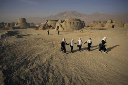 Afghan girls walk past a brick factory on their way to their school in Kabul, Afghanistan, Thursday, June 26, 2008. In western Kabul there are about 50 factories where brick makers fire handmade bricks used for the reconstruction of buildings destroyed over two decades of war.