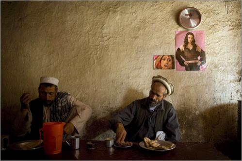 Afghan men eat their lunch in a restaurant decorated with posters of Bollywood actresses in downtown Kabul, Afghanistan, Friday, June 27, 2008.