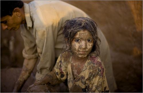A girl with her face covered with mud helps her brother to rehabilitate their house in a refugee camp on the outskirts of Islamabad, Pakistan, Friday, June 20, 2008. Some thousands of Afghan families who fled their country due to war and fighting among war lords are forgotten by the international community who will observe the World Refugee Day on Friday.