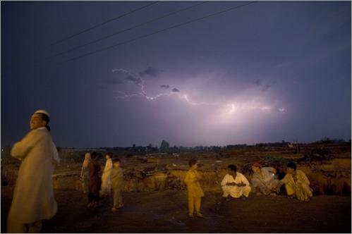 Lightning sparks across the night sky as Pakistani people stand next to the road on the outskirts of Islamabad, Pakistan, Saturday, June 21, 2008.