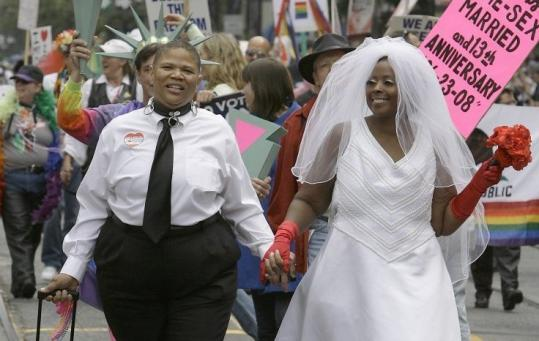 Sherri Black-White (left) and partner Shidiva Black-White walk yesterday in San Francisco's gay pride parade.