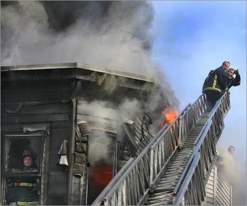 Buy this picture! Firefighters yell to colleagues below to move them away from the flames to the safety of the roof at right during the Blue Hill Avenue fire in 2007.