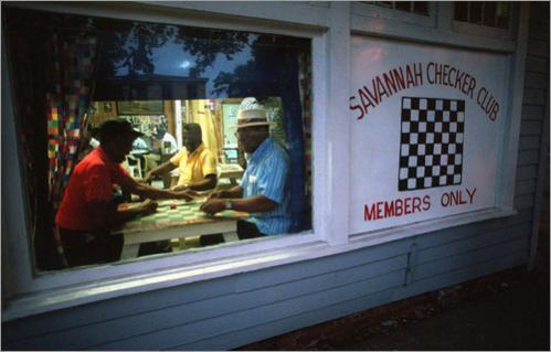 Buy this picture! With the rising moon outside their picture window, Joe 'Porky' Patterson, left, and Thomas 'Tommy' Jones play a game in the Savannah Checker Club on West 39th Street in Savannah, GA.. The all-black, all-male club has been in this location for sixteen years.