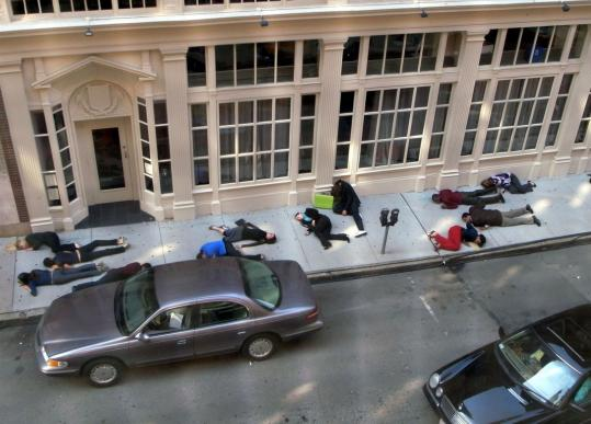 Extras play dead on Water Street in Boston during the filming of the Bruce Willis movie 'The Surrogates.'