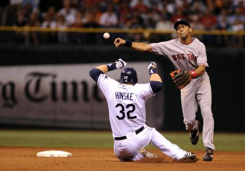 Red Sox shortstop Julio Lugo shuffles out of the way of oncoming Eric Hinske while trying to turn a double play.