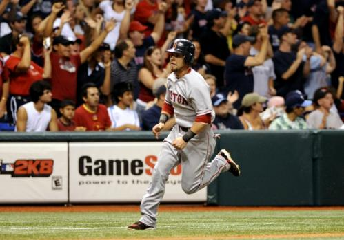 Red Sox second baseman Dustin Pedroia rounds third base and heads home for a run.