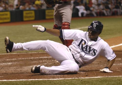 Willy Aybar (16) of the Rays slides across home plate, scoring a run for Tampa Bay.