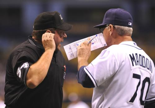 Manager Joe Maddon, right, of the Tampa Bay Rays shares a lineup change with home plate umpire Sam Holbrook.
