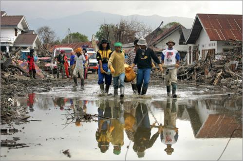 Bodies were still being discovered by the thousands each day, even a month after the December 26 tsunami. Here workers haul a particularily heavy body through a puddle toward the body truck.