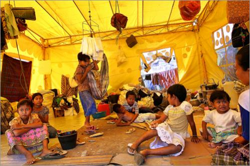 These children pass the hot daylight hours in a government-supplied refugee tent that five families share. They are all from the same village named Lamboro Nejid, which is eight kilometers from Banda Aceh. Their homes were all destroyed by the December 26 tsunami. At the time of this photo, they were humming along to the 4:00 pm prayers broadcast from a nearby mosque.