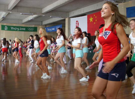 New England Patriots cheerleader Julie Warner (far right) and other members of the squad lead a class in Beijing.