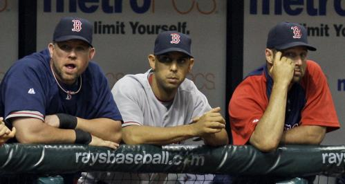 Boston Red Sox players (from left) Sean Casey, Alex Cora, and Tim Wakefield look on as the Tampa Bay Rays score six runs in the seventh inning.