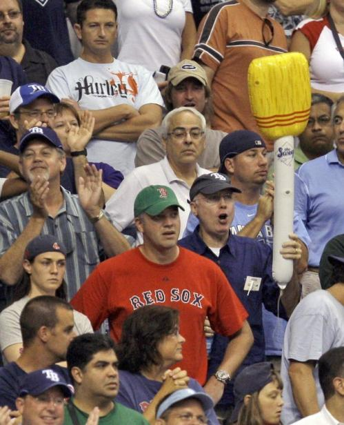 A Tampa Bay Rays fan celebrates with an inflatable broom next to a Boston Red Sox fan.
