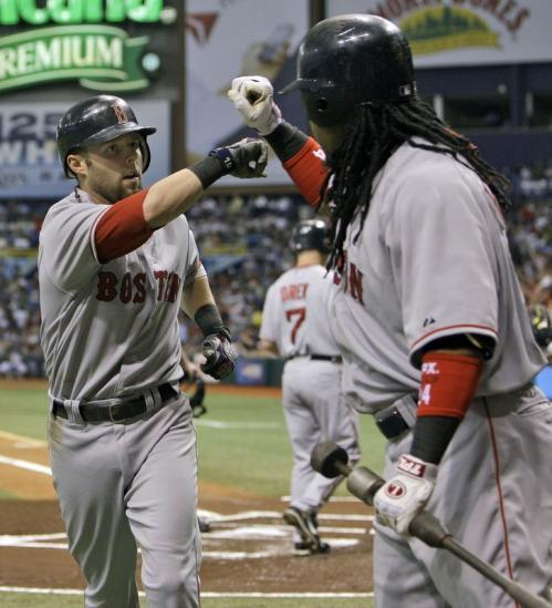 Boston Red Sox's Dustin Pedroia, left, bumps fists with teammate Manny Ramirez, right, after hitting a first-inning home run off Tampa Bay Rays' Scott Kazmir.
