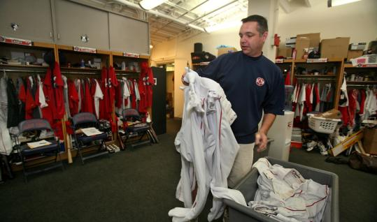Steve Murphy, a Red Sox clubhouse worker from Danvers, sorts through the team's laundry.