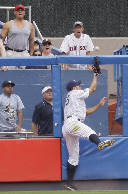 The ball pops out of the glove of Damon as he slams into the wall in left field trying to corral Youkilis's fly ball.