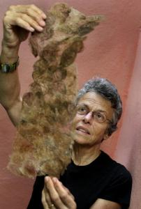 Catherine Craig, an expert on spider webs, holds up wild silkworm cocoons that have been washed, flattened and glued.