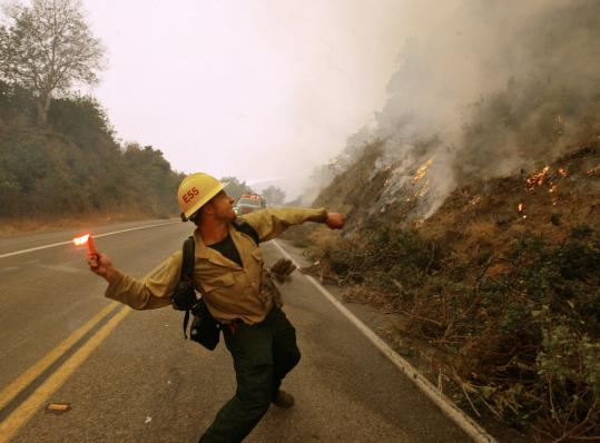 A firefighter threw flares onto a hillside during a backburn operation yesterday in Big Sur, Calif.