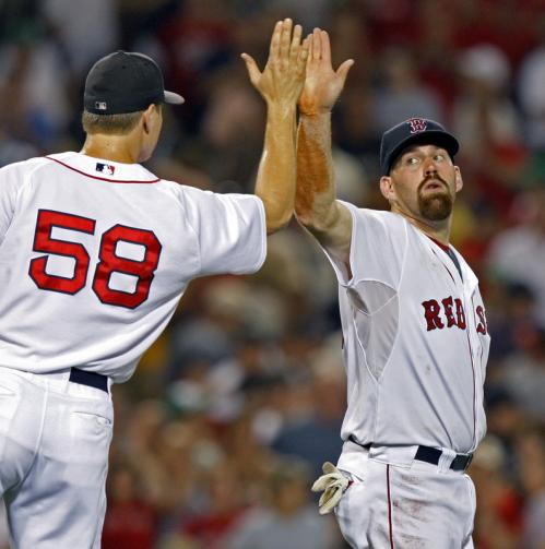 Jonathan Papelbon and Kevin Youkilis exchange a high-5 after recording the final out of the game.