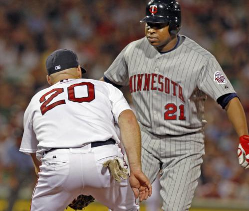 Red Sox first baseman Kevin Youkilis tags the Twins Delmon Young to finish off an unassisted double play in the seventh inning.