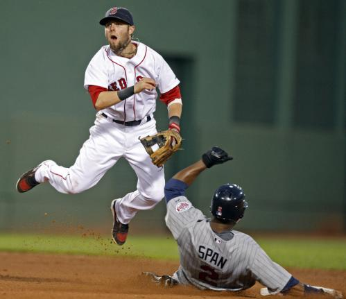 Red Sox second baseman Dustin Pedroia completes a fifth-inning double play hit into by the Twins Carlos Gomez (not pictured) after forcing Denard Span at second base.