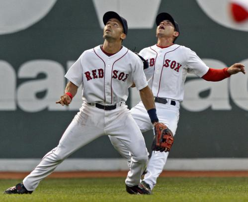 Red Sox shortstop Julio Lugo (left) and left fielder Jacoby Ellsbury (right) both eye a Justin Morneau fly ball in the fourth inning. Ellsbury called off Lugo and made the catch.
