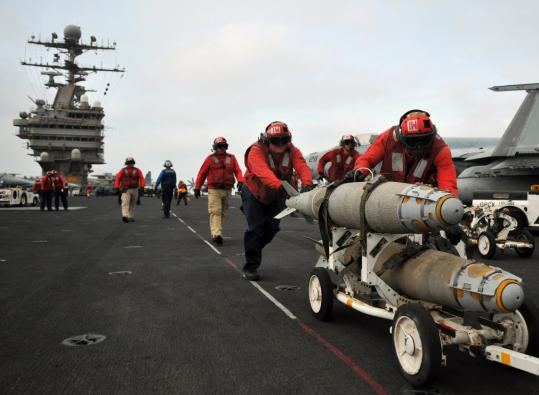 Bombs were pushed into position to be loaded onto aircraft yesterday aboard the USS Abraham Lincoln. The carrier was moved out of the Persian Gulf and to the Gulf of Oman.