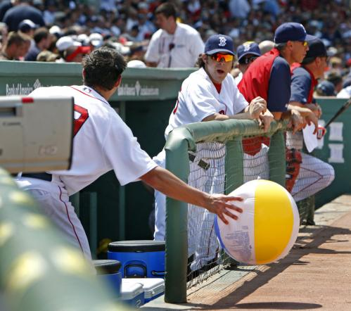 It was hot enough at Fenway to be a beach day, and when a stray beach ball came out of the stands and landed in front of the Red Sox dugout, Boston starting pitcher Josh Beckett (left) came out and grabbed it, then tossed it back to the fans.
