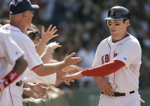 Jacoby Ellsbury is welcomed to the Red Sox dugout after scoring on a three-run double by Dustin Pedroia in the seventh inning.