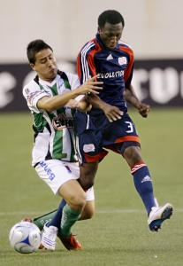 The Revolution's Sainey Nyassi (right) and Santos Laguna's Osmar Mares fight for possession during the first half.