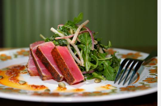 The seared Atún is rubbed with adobo and served alongside an arugula salad with sun-dried tomato vinaigrette.