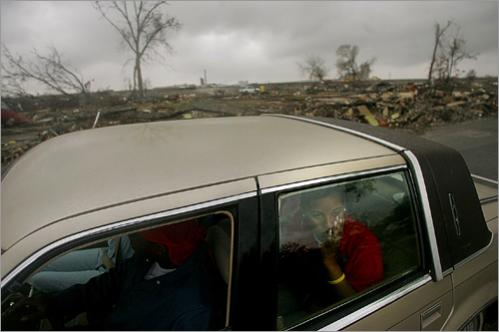 Members of the Berryhill family stare out at the devastion of their old neighborhood in New Orleans' Lower Ninth Ward, Tuesday January 17 2006. Directly behind their car is the lot where the Berryhill's home used to sit until the levee protecting the neighborhood was breached by flood waters from Hurricane Katrina sending a wave of water into the neighborhood and destroying their home.