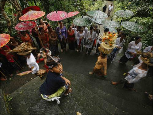 A child watches as people walk by carrying holy water for the procession of Pelebon on July 13, 2008.