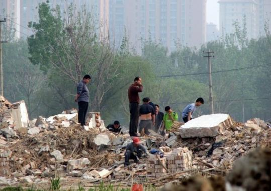 Scavengers picked through the remains of Wang Lianmin's house, razed to make way for Olympics-related construction
