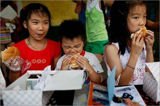 Eight-year-old twins Rachel (left) and Victoria Shen and their brother, 3-year-old John, ate their lunches at Snug Harbor Elementary School in Quincy yesterday.