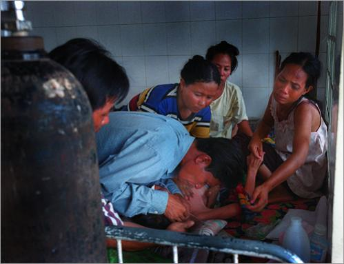 Hang Por gives his wife, Ly Chanthon, 26, mouth to mouth in an attempt to revive her as one of her sisters pushes on her chest in Phnom Penh. Ly slipped into a coma and lingered for days before succoming to tuberculosis.
