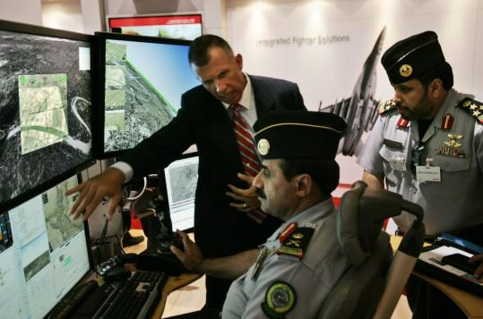 Mark Bigham (left) shows Raytheon's control system for unmanned aircraft. A key factor was making the system more intuitive - replacing keystrokes with a game console - on the theory that thumbs are the most accurate way to control a craft.
