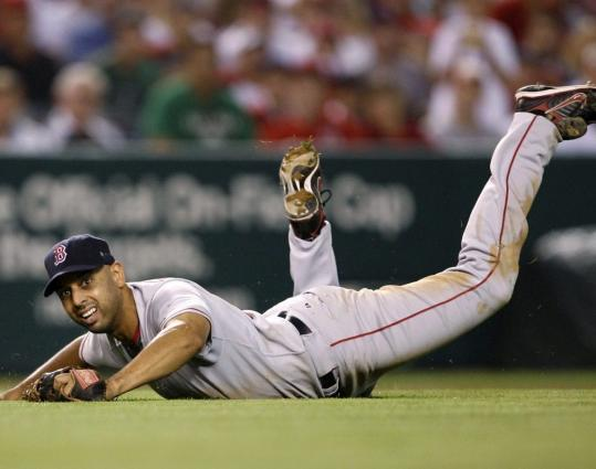 Red Sox shortstop Alex Cora flops to the grass after flopping on a play, mishandling a grounder by the Angels' Torii Hunter for a