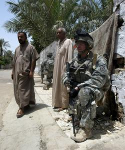 As Iraqis walked past, a US soldier stood guard over the site where an IED had detonated in western Baqubah, on Sunday. Iraq is one of the top issues in the US presidential campaign.