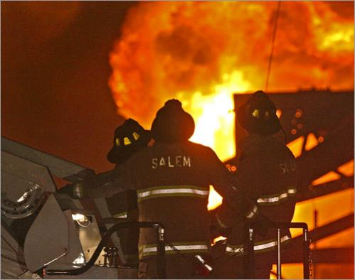 An explosion that reverberated for miles reduced a chemical plant to an ashen heap and flattened homes in Danvers before Thanksgiving Day in 2006, but miraculously took no lives. Salem firefighters watch as flames rise from the site.