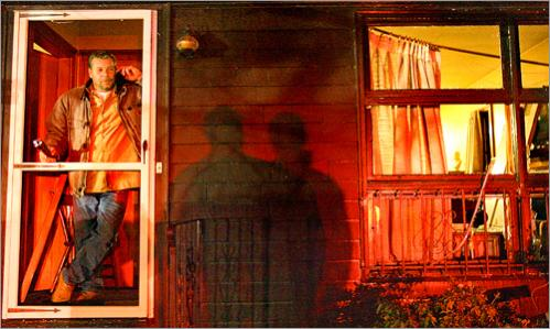 Jeff Moore stands in the doorway of his mother's home, directly across the street from an explosion and fire on Water St. in Danvers, Wednesday, November 22, 2006. Marilyn Moore, 80, escaped with no injuries, but her home suffered extensive damage.