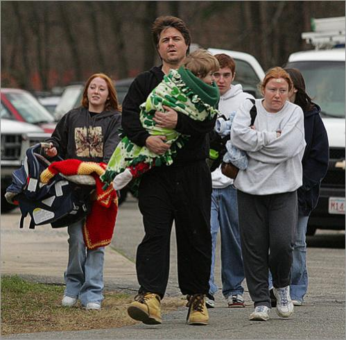 Tim Barry carries his son Noah as he and his family arrive at Danvers High School seeking shelter after their Bates Street home was lost in the explosion.