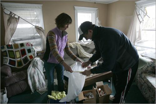 Maureen and Bill Merritt of Danvers help Bill's father George retieve medications from his home on Riverside Street following the early morning explosion. Merritt was allowed to return to his home briefly with a Danvers Police officer to retrieve medications, prescription glasses and shoes for his wife.