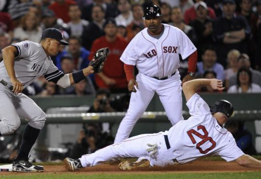 Kevin Youkilis beats Alex Rodriguez's tag after going from first to third on David Ortiz's first-inning single. He later scored.