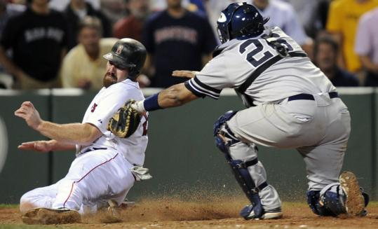 Kevin Youkilis crosses the plate with the ninth Red Sox run, eluding Jose Molina's tag to score on Manny Ramírez's single in the sixth inning.