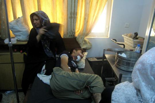 A woman sat at a hospital in Kirkuk, Iraq, yesterday with a man injured in a